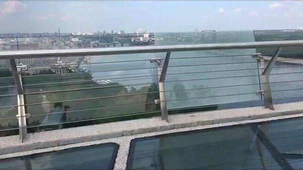 Покрытое трещинами боковое стекло на новом пешеходно-велосипедном мосту в Киеве, Украина. Стоп-кадр видео очевидца