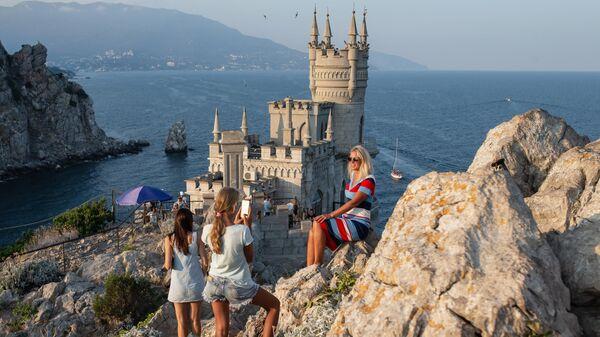 Отдыхающие фотографируются возле замка Ласточкино гнездо на береговой скале в поселке Гаспра в Крыму