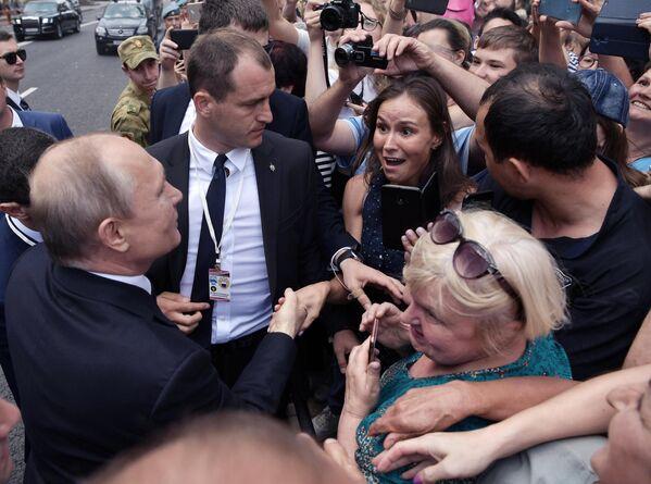 Президент РФ, верховный главнокомандующий Владимир Путин общается с горожанами во время прогулки по Адмиралтейской набережной после парада по случаю Дня Военно-морского флота РФ в Санкт-Петербурге