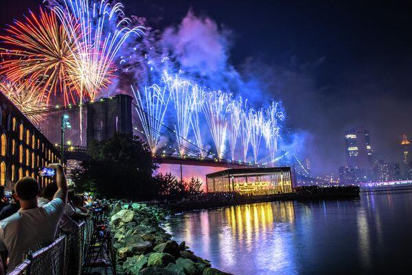 Люди наблюдают салют над Бруклинским мостом в Нью-Йорке во время празднования Дня независимости США