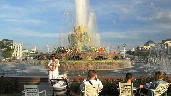 Люди отдыхают у фонтана Каменный цветок на ВДНХ в Москве