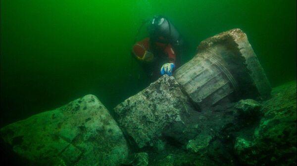 Археолог-водолаз на месте затопленного древнего города Гераклион в Средиземном море близ Александрии в Египте