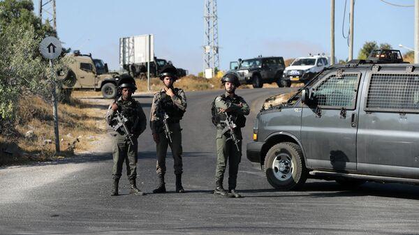 Израильские военные недалеко от места, где был найден убитым израильский солдат на Западном берегу