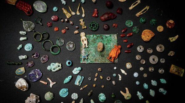 Амулеты, драгоценные камни и декоративные элементы из фаянса, бронзы, кости и янтаря найденные в результате раскопок в Помпеях