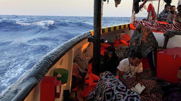 Мигрант читает Коран на борту судна