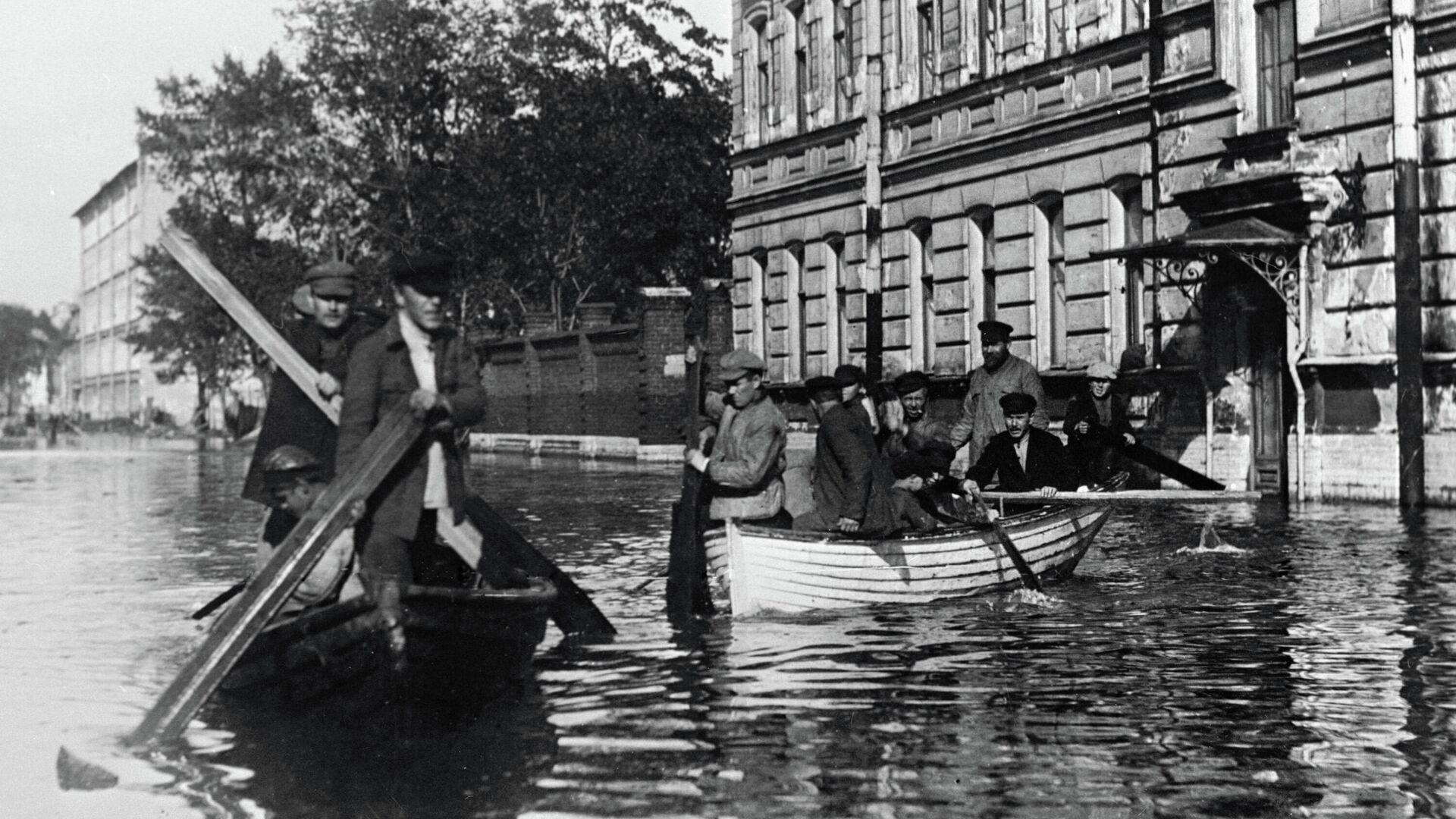 Жители города, затопленного при наводнении, передвигаются по улицам в лодках - РИА Новости, 1920, 23.09.2021