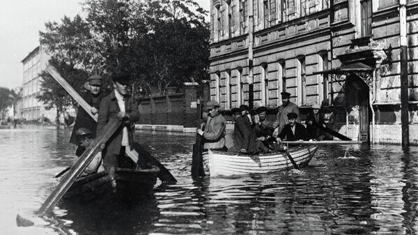 Жители города, затопленного при наводнении, передвигаются по улицам в лодках