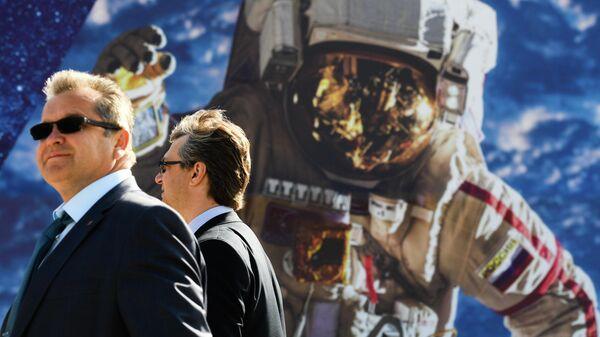 Посетители у стенда с фотографией российского космонавта на Международном авиационно-космическом салоне МАКС-2019