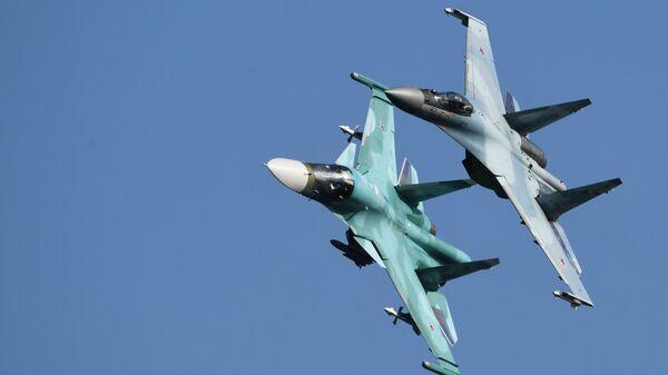 Российские многоцелевые истребители Су-35С (справа) и Су-34 выполняют полет на Международном авиационно-космическом салоне МАКС-2019