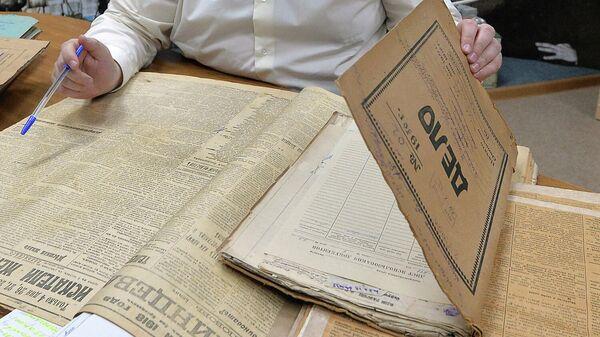 Сотрудник разбирает папки с документами в Государственном архиве