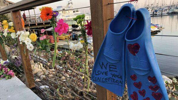 Цветы в гавани, где погибло 30 человек во время пожара на лодке Зачатие в Южной Калифорнии