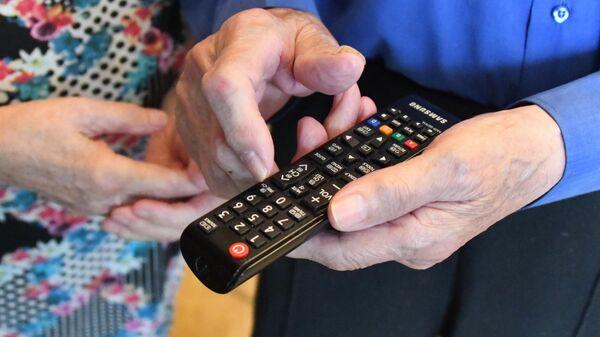 Телевизионный пульт в руке пожилого мужчины