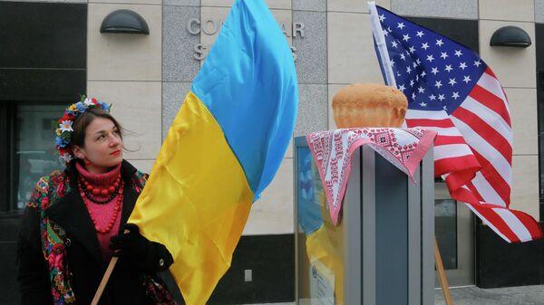 Женщина держит флаг Украины рядом с посольством США в Киеве