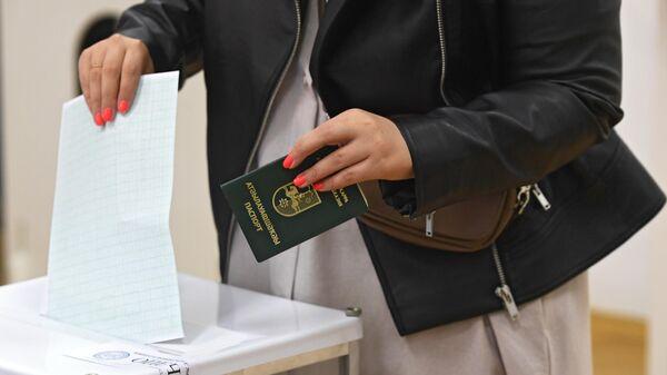 Избиратель бросает в урну бюллетень в день второго тура выборов президента Абхазии на избирательном участке в Москве