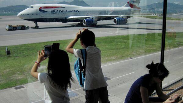 Пассажиры фотографируют Боинг 747 авиакомпании British Airways в международном аэропорту Гонконга