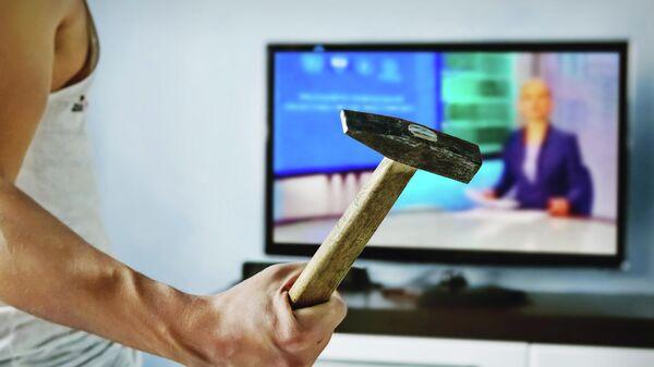 Мужчина с молотком перед телевизором