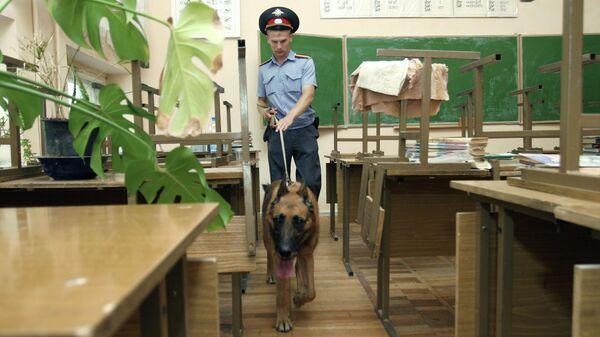 Сотрудник полиции проверяет с собакой учебный класс