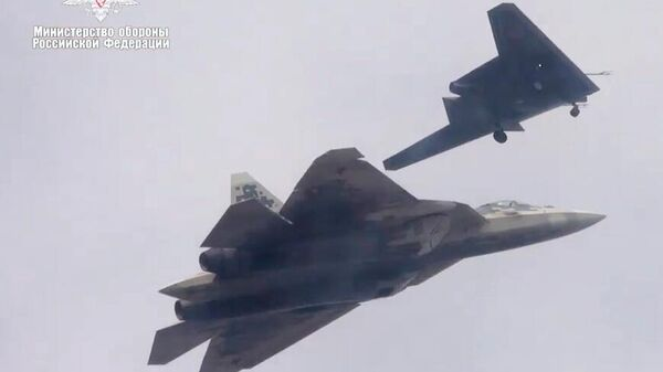 Новейший ударный беспилотник Охотник во время первого совместного полета с истребителем Су-57