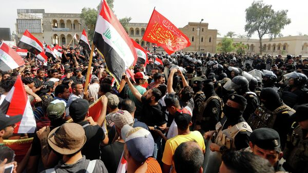 Сотрудники полиции и участники акции протеста на площади ат-Тахрир в Багдаде, Ирак. 1 октября 2019