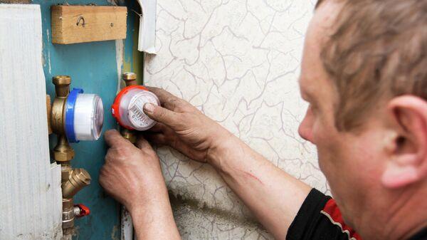 Сантехник осуществляет установку прибора индивидуального учета водопотребления в квартире жилого дома в Иркутске