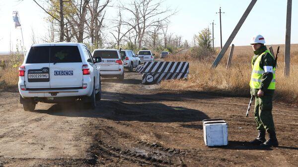 Автомобили наблюдателей ОБСЕ на пропускном пункте в селе Петровское в Донецкой области, где должен состояться отвод сил бойцов подразделений Донецкой народной республики