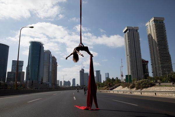 Израильская акробатка Tel Karassin выступает на пустой автомобильной трассе во время празднования Йом-Киппура в Тель-Авиве