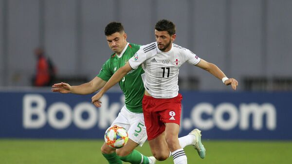 Нападающий сборной Грузии Георгий Квилитая (справа) и защитник сборной Ирландии Джон Иган