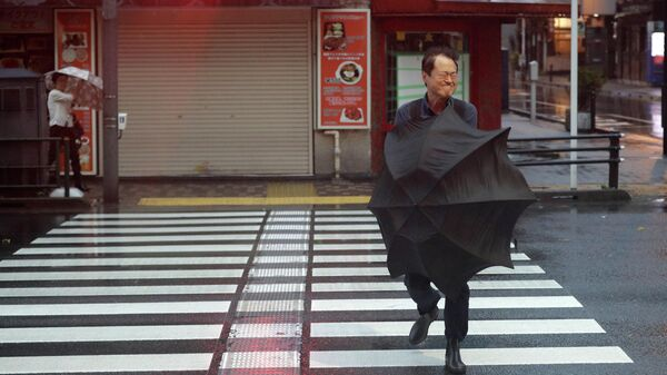 Мужчина на улице Токио во время прохождения тайфуна Хагибис в Японии