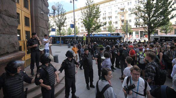 Участники несанкционированной акции в поддержку кандидатов в депутаты Мосгордумы и полиция у здания мэрии Москвы