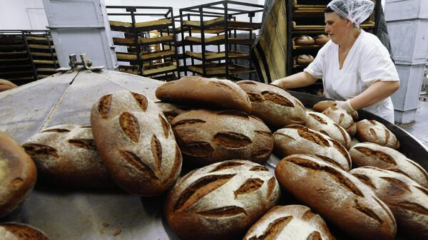 Укладчик хлеба  выкладывает хлеб на лотки
