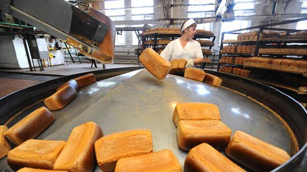 Работница укладывает хлеб в лотки в цехе готовой продукции
