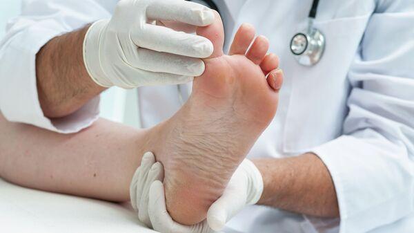 Доктор осматривает ноги пациента
