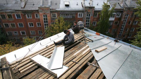 Рабочие перекрывают крышу многоэтажного дома