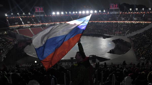A spectator waves the Russian flag ahead of the opening ceremony of the Pyeongchang 2018 Winter Olympic Games at the Pyeongchang Stadium on February 9, 2018. (Photo by LOIC VENANCE / AFP)