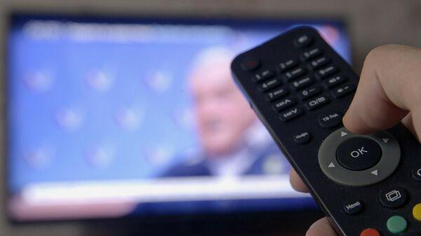 Человек держит пульт дистанционного управления устройством захвата цифрового сигнала