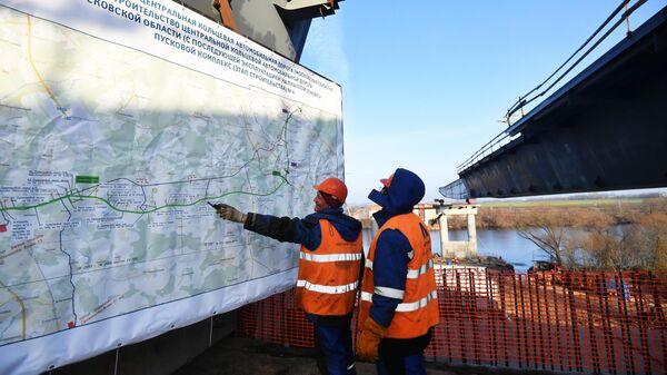 Рабочие осматривают план строительства Центральной кольцевой автомобильной дороги в Москве