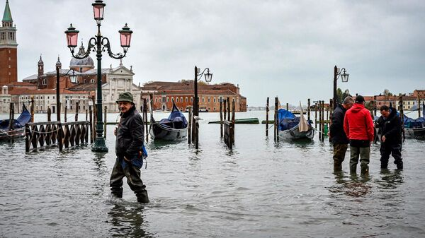 Прохожие на одной из улиц в Венеции во время наводнения