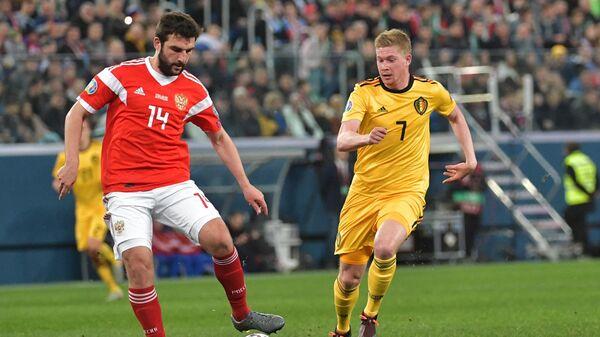 Защитник сборной России Георгий Джикия (слева) и полузащитник сборной Бельгии Кевин де Брейне