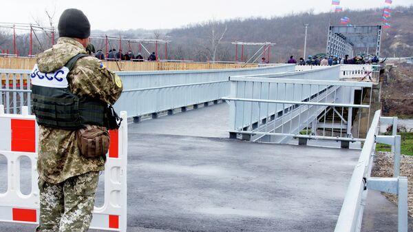 Военный у восстановленного пешеходного моста через реку Северный Донец у КПП Станица Луганская