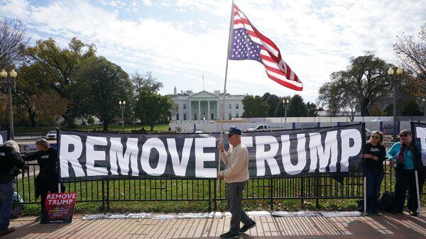 Активисты держат плакат с просьбой об импичменте президента США Дональда Трампа