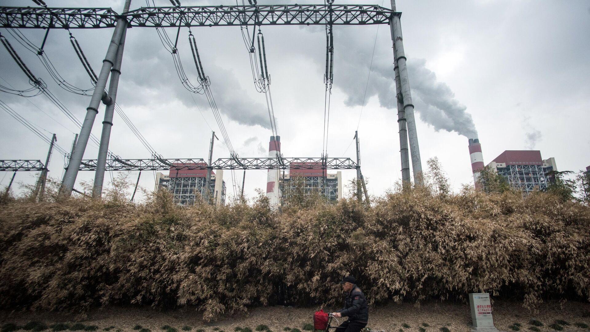 Мужчина проезжает мимо угольной электростанции Shanghai Waigaoqiao Power Generator Company в Шанхае, Китай  - РИА Новости, 1920, 13.05.2021