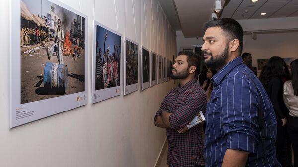Посетители на выставке победителей Международного конкурса фотожурналистики имени Андрея Стенина в галерее AIFACS Gallery в Нью-Дели. 29 ноября 2019