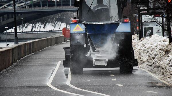 Сотрудник коммунальной службы обрабатывает противогололедными реагентами проезжую часть дороги