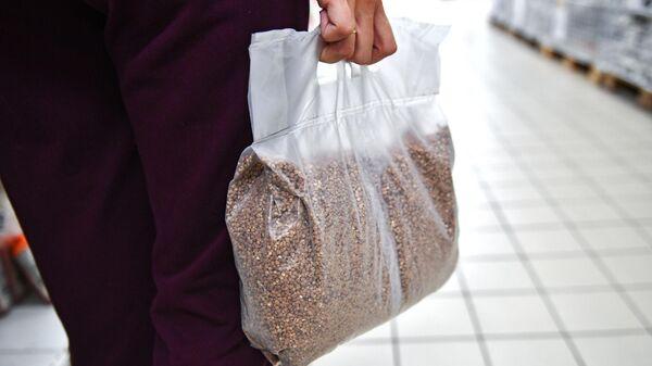 Покупательница несет пакет с гречневой крупой в одном из магазинов Симферополя