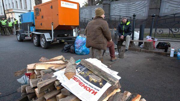 Участники акции протеста греются у открытого огня возле здания администрации президента Украины в Киеве