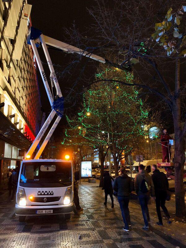 Рабочие устанавливают Рождественскую ель на одной из улиц в центре Праги.