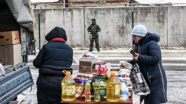 Российский пограничник наблюдает за стихийным рынком на украинской стороне