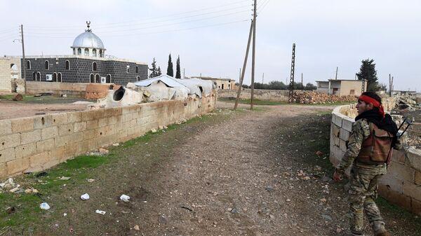 Сирийский ополченец в освобожденном от боевиков поселке Сукейя в провинции Идлиб
