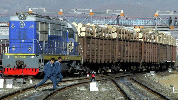 Железнодорожные рабочие возле поезда, перевозящего древесину, импортируемую из России, на железнодорожной станции в Суйфэньхэ, Китай