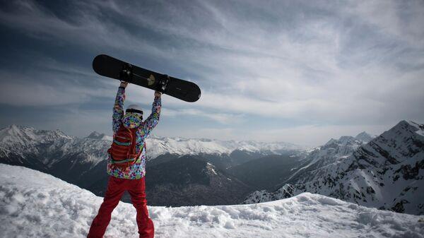 Сноубордист на высоте 2320 метров на вершине Роза Пик на горном курорте Роза хутор в Красной поляне